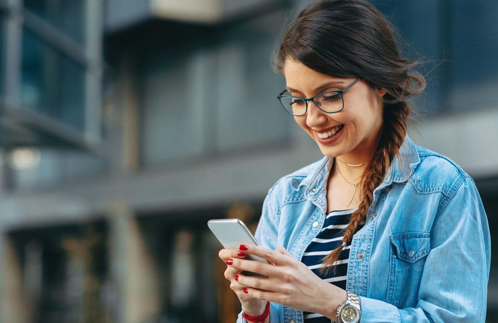 Jeune femme utilisant son smartphone en souriant